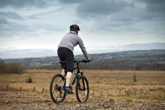 en mand cykler på mark